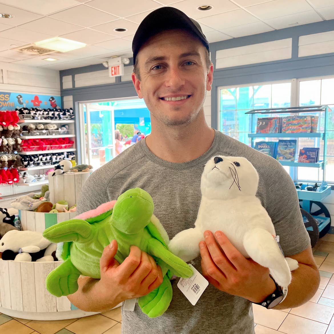 A Caucasian male wearing a grey t-shirt and black cap holds a stuffed turtle and arctic seal in a shop.