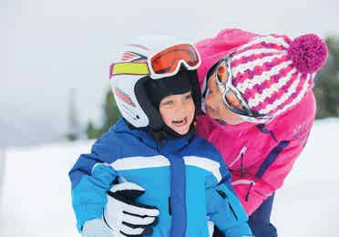 Young child and adult skiing on a snowy mountain
