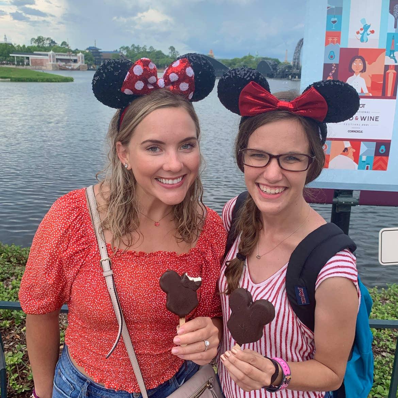 Two caucasian women wearing Minnie ears stand near the World Showcase Lagoon while holding Mickey Ice Cream bars.