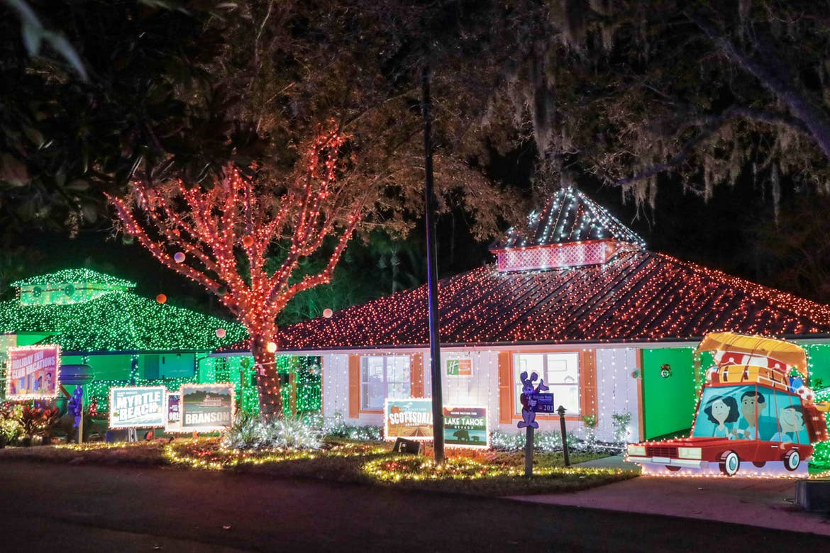 A nighttime exterior of the HICV Villa with colorful string lights and giant postcard decorations.
