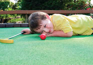 A child on lying on the green at a mini golf course looking at a red golf ball and holding a yellow putter
