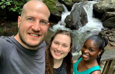 A caucasian man (left), a caucasian woman (middle) and an African American woman stand in front of the Anna Ruby Falls waterfall surrounded by lush green woods.