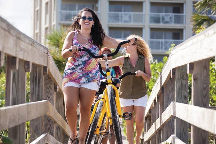 Two women pushing bicycles down bridge leading to the beach