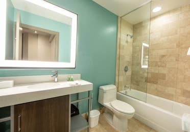 One bedroom villa bathroom with shower/tub combination, toilet and sink with lighted mirror at New Orleans Resort in Louisiana.
