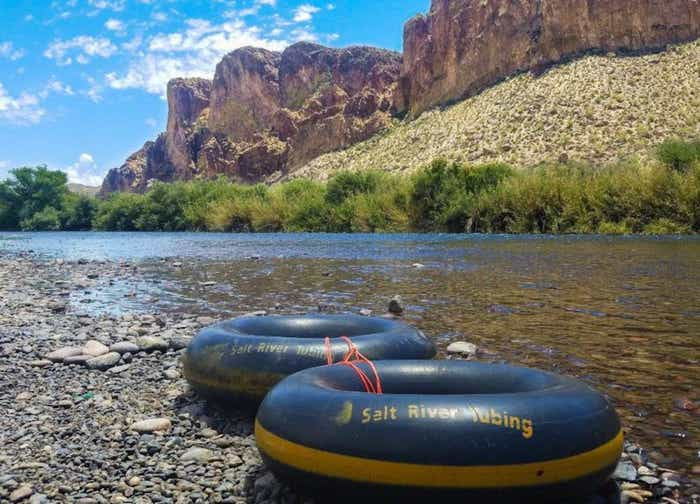Salt River Tubing floats sitting along the bank of the Salt River with mountain ridges in the distance.