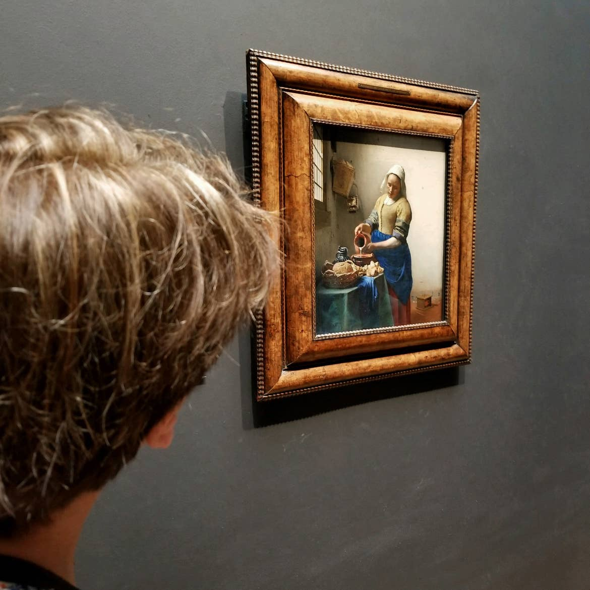 A woman looks at the famous 'The Milkmaid' painting by Johannes Vermeer located at the Rijksmuseum in Amsterdam, Netherlands.