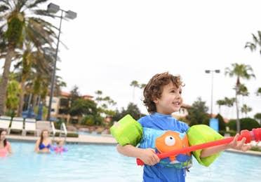 Young child standing by pool at Orange Lake Resort near Orlando, Florida