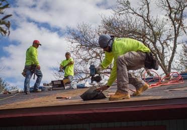 Three men nailing new shingles onto a roof