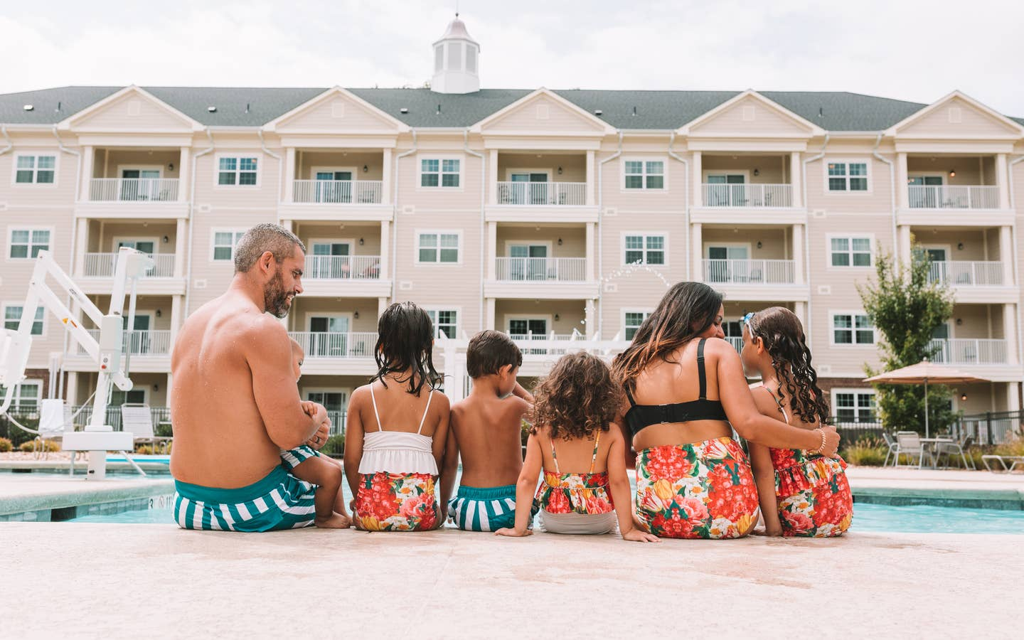 Mother, father, and five children sitting at the edge of a pool at Holiday Inn Club Vacations Williamsburg Resort