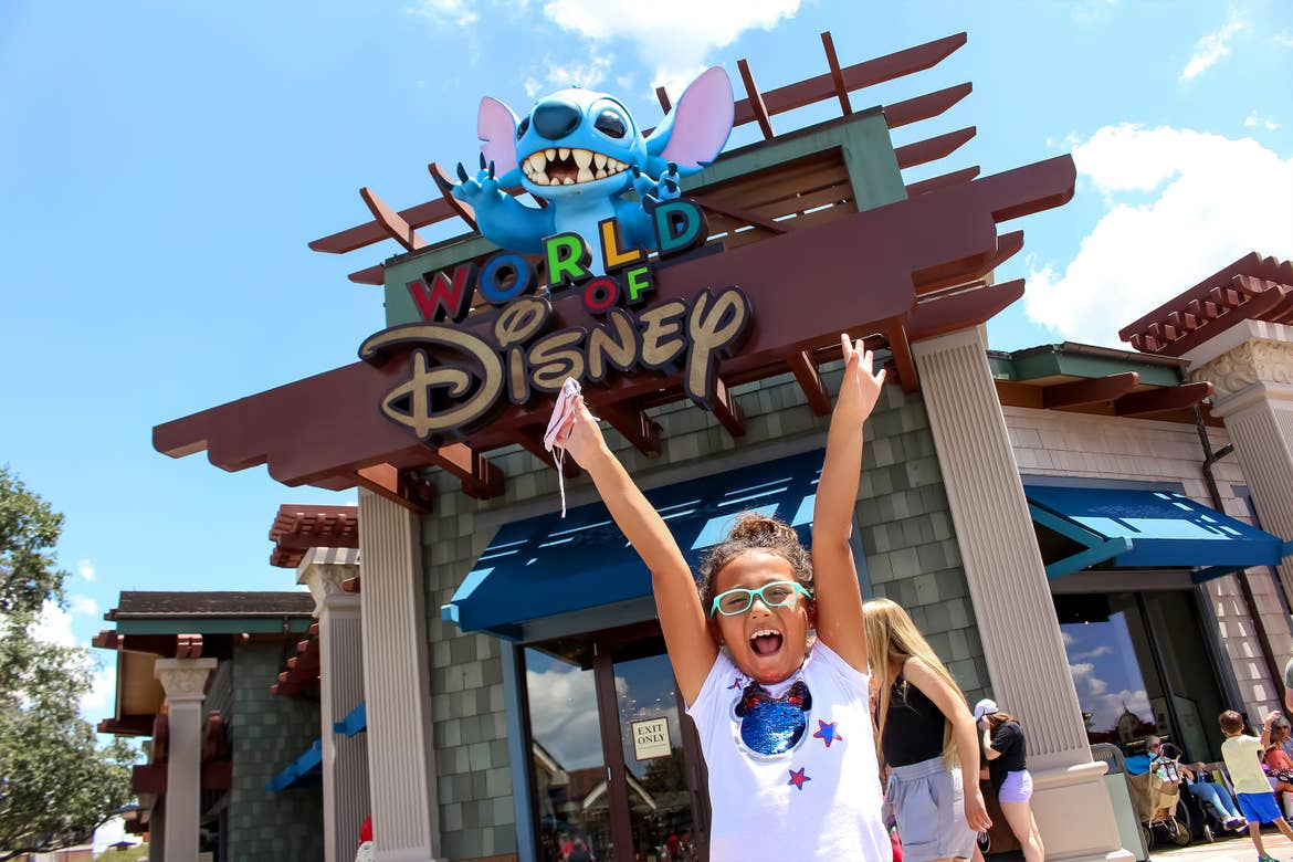 An Asian girl wearing a white, sparkly Minnie Mouse t-shirt and blue glasses poses with her arms up and holds a safety mask in front of the 'World of Disney' storefront signage with a large statue of 'Stitch' from Disney's Lilo & Stitch