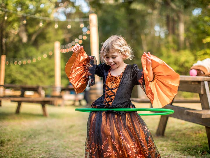 Young child in a Halloween costume hula-hooping at Falladays.