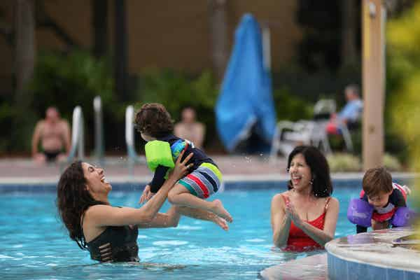 Mother catching her child as he jumps into the pool.