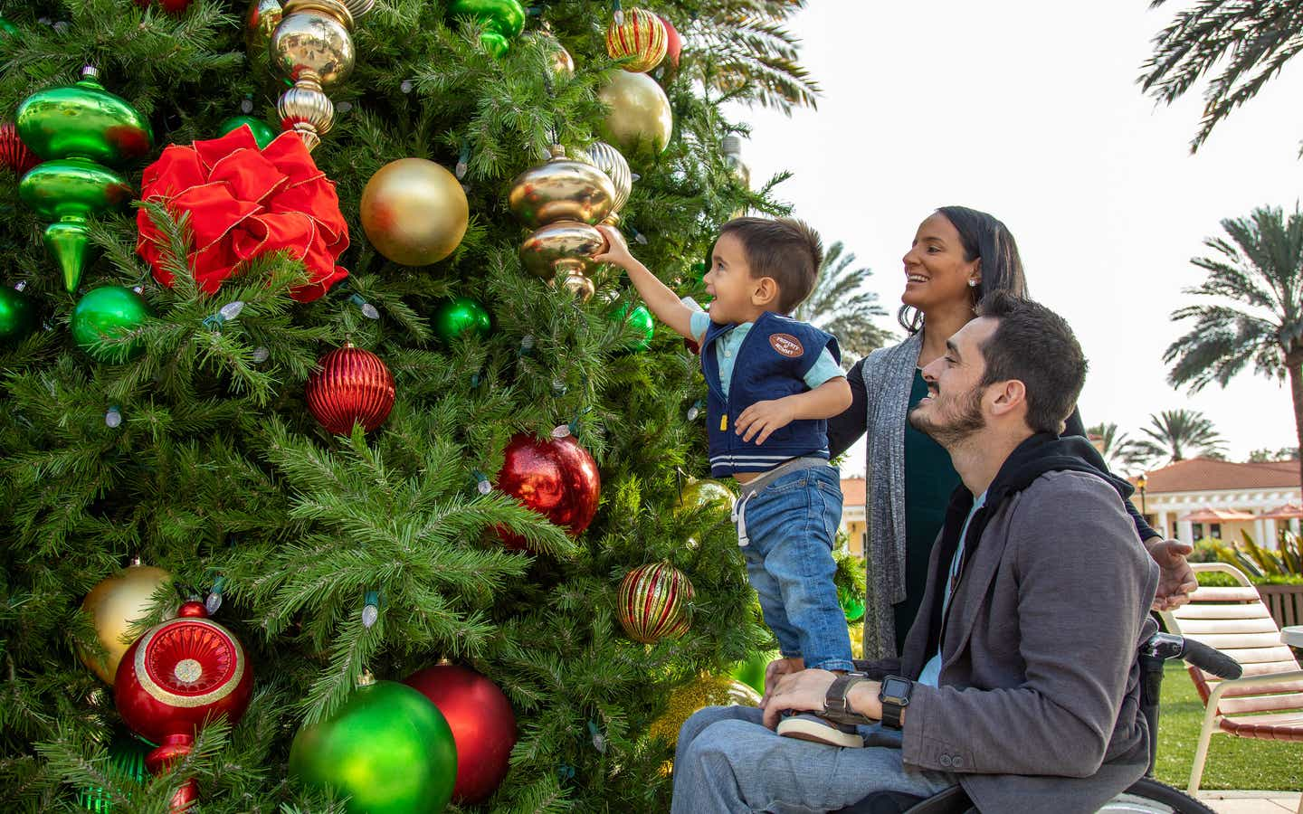 Author, Danny Pitaluga (right) sits in his black wheelchair wearing a charcoal hoodie as his wife, Val (middle), and his son, Joey (left), stands on Danny's lap to decorate a Christmas tree outdoors.