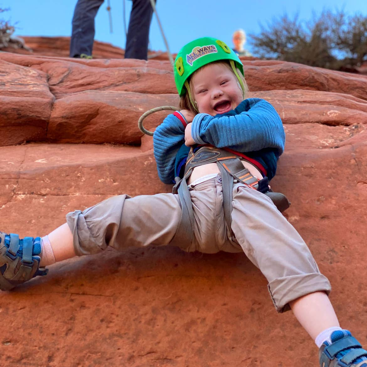 Featured Contributor, Melody Forsyth's daughter, Ruby, wears a blue jacket and green safety helmet and harness while rappelling down an orange rock formation.