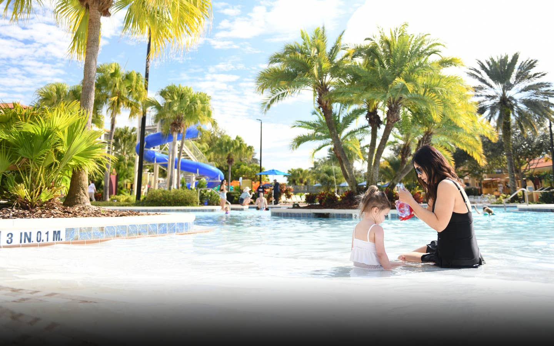 Adult and child sitting in zero-entry pool at Orange Lake Resort near Orlando, Florida.