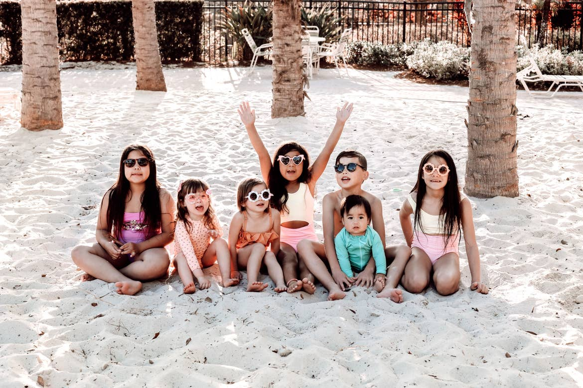 Seven young children sit on the white sands wearing swimming attire and sunglasses.