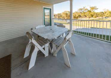 Furnished balcony with table and four chairs in a presidential two bedroom villa at Piney Shores Resort in Conroe, Texas