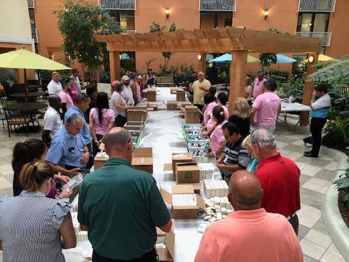 Volunteers sorting cleaning and hygiene products into boxes