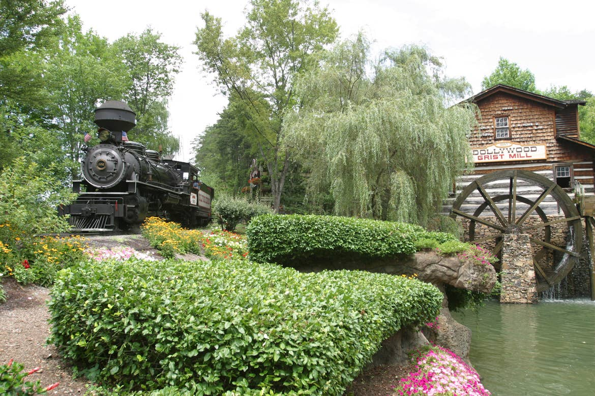 A black steam train at Dollywood rides past a gristmill.