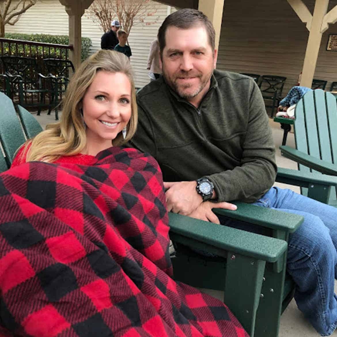 Author, Amanda Nall (left) sits under a cozy festive throw blanket with her husband outdoors.