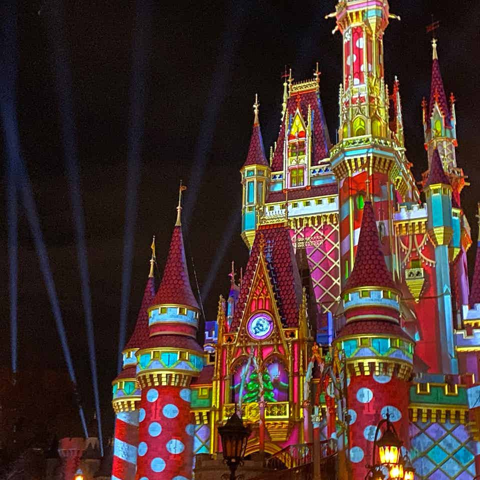 Cinderella's Castle at Magic Kingdom Park at Walt Disney World® Resort is illuminated with holiday projections at night.