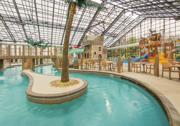 Indoor lazy river and water feature in background at Pirate's Cay Waterpark at Fox River Resort in Sheridan, Illinois