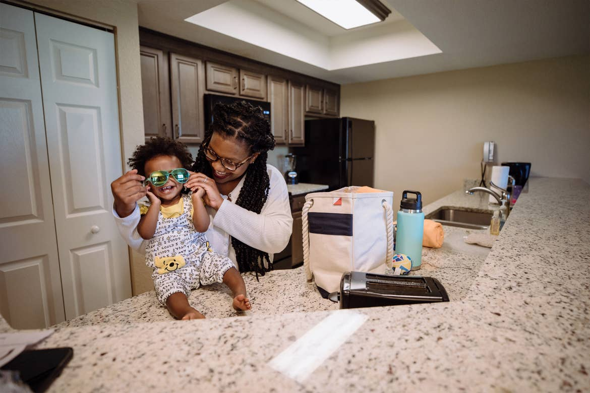 Krystin Godfrey (right) helps her daughter, Creed (left), put on a pair of blue sunglasses on the countertop of their three-bedroom villa in North Village at our Orange Lake Resort located in Orlando, FL.