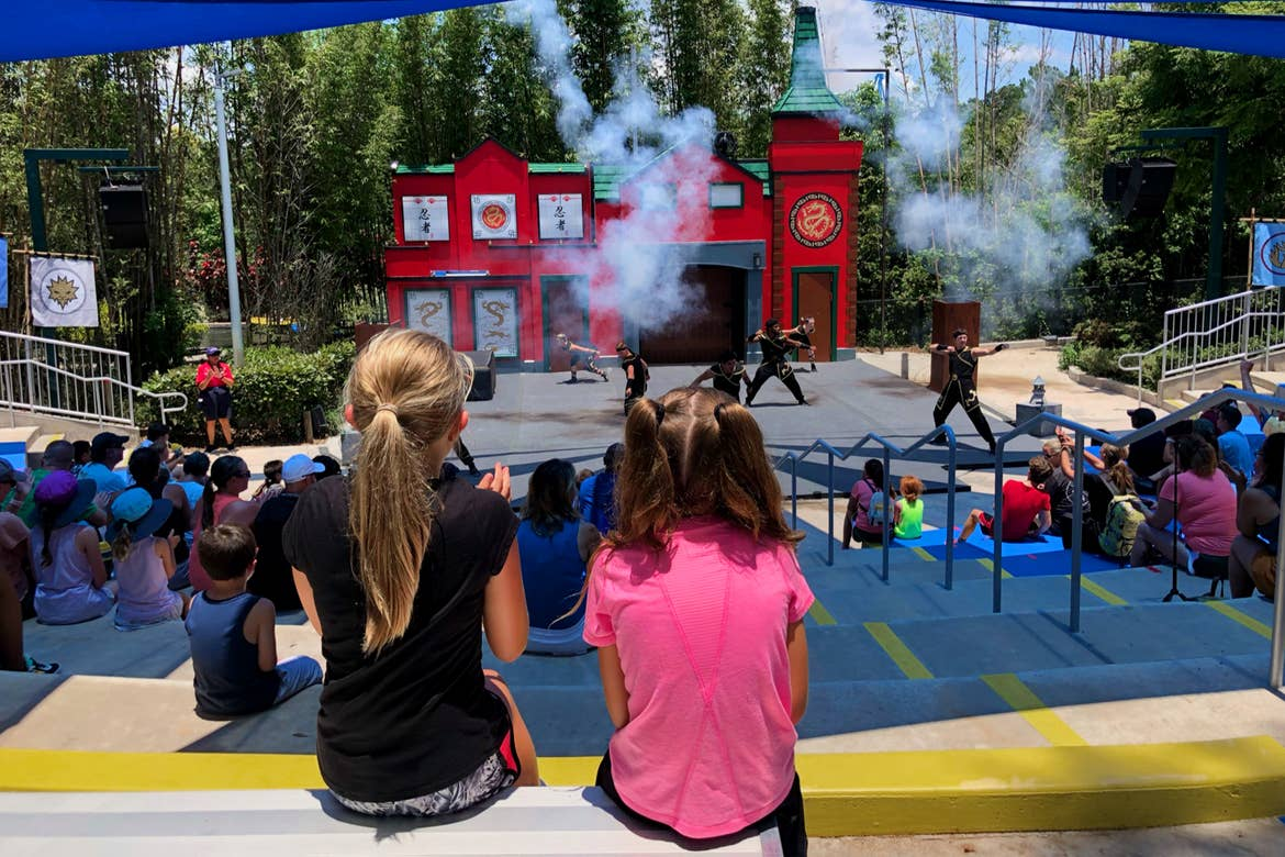 Two young girls sit in an outdoor theater watching a stage stunt show.