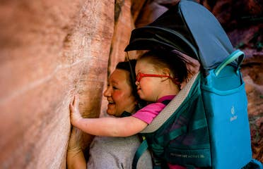 Featured Contributor, Melody Forsyth (left), backpacks with her daughter, Ruby (right), as they touch some rock formations.