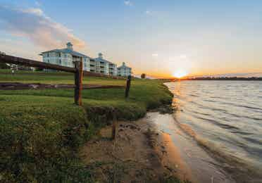View of property buildings near water at Piney Shores Resort in Conroe, Texas