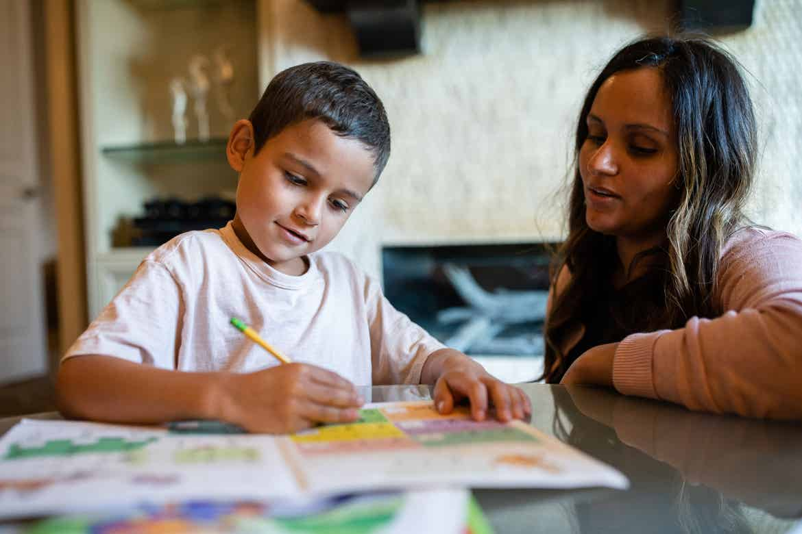 Brenda (right) helps her son (left) with his homework assignments.