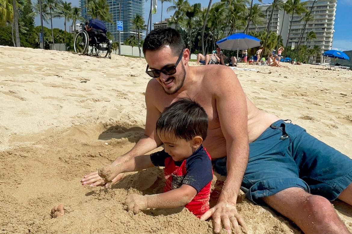 Featured Contributor, Danny Pitaluga (back) and his son, Joey (front) play with sand on the beach in swimwear.