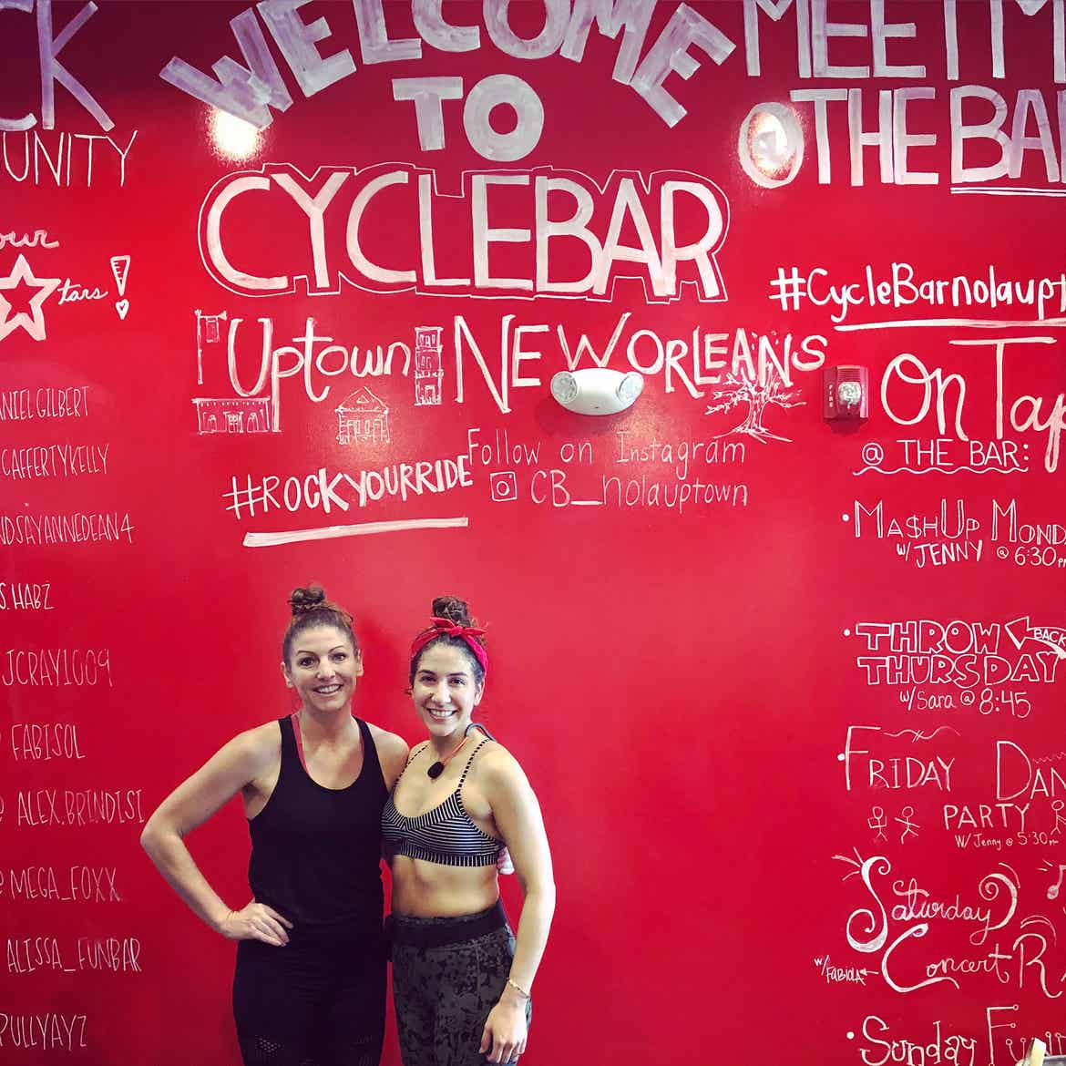 Co-author, Christine (left), wears a black tank top and shorts while posing with a fellow cycle bar instructor at New Orleans location.
