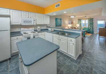 Kitchen with island, fridge, oven, microwave, dishwasher, and sink in a two-bedroom villa at Panama City Beach Resort