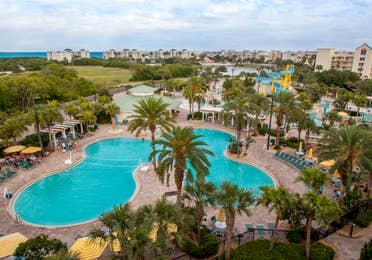 Aerial view of resort pool surrounded by palm trees at Cape Canaveral Beach Resort.