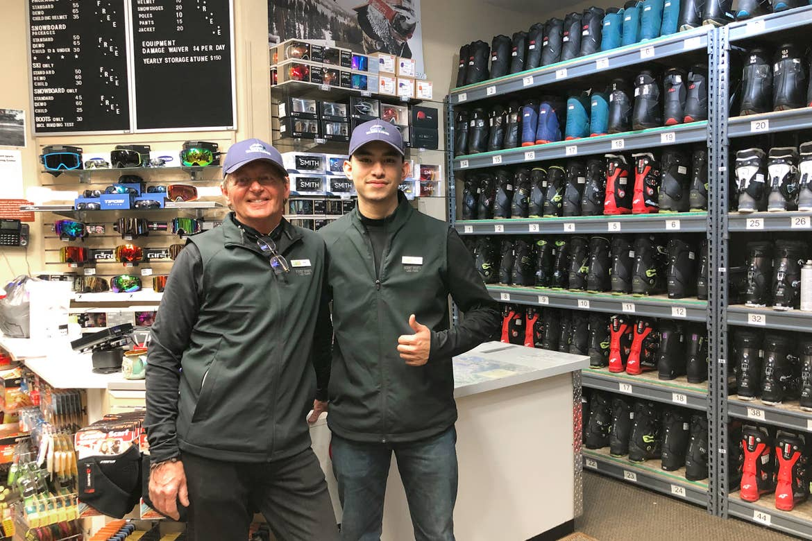Team Members, Bert (left), and (right) stand in the Resort Sport Shop surrounded by ski gear.