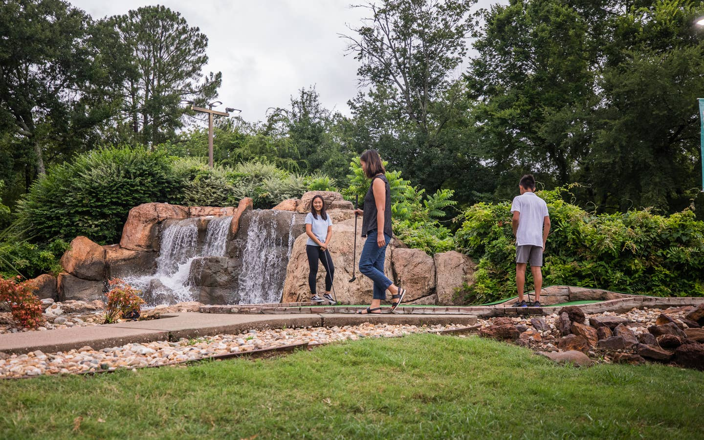 Three guests playing mini golf in front of waterfall at Villages Resort in Flint, Texas.