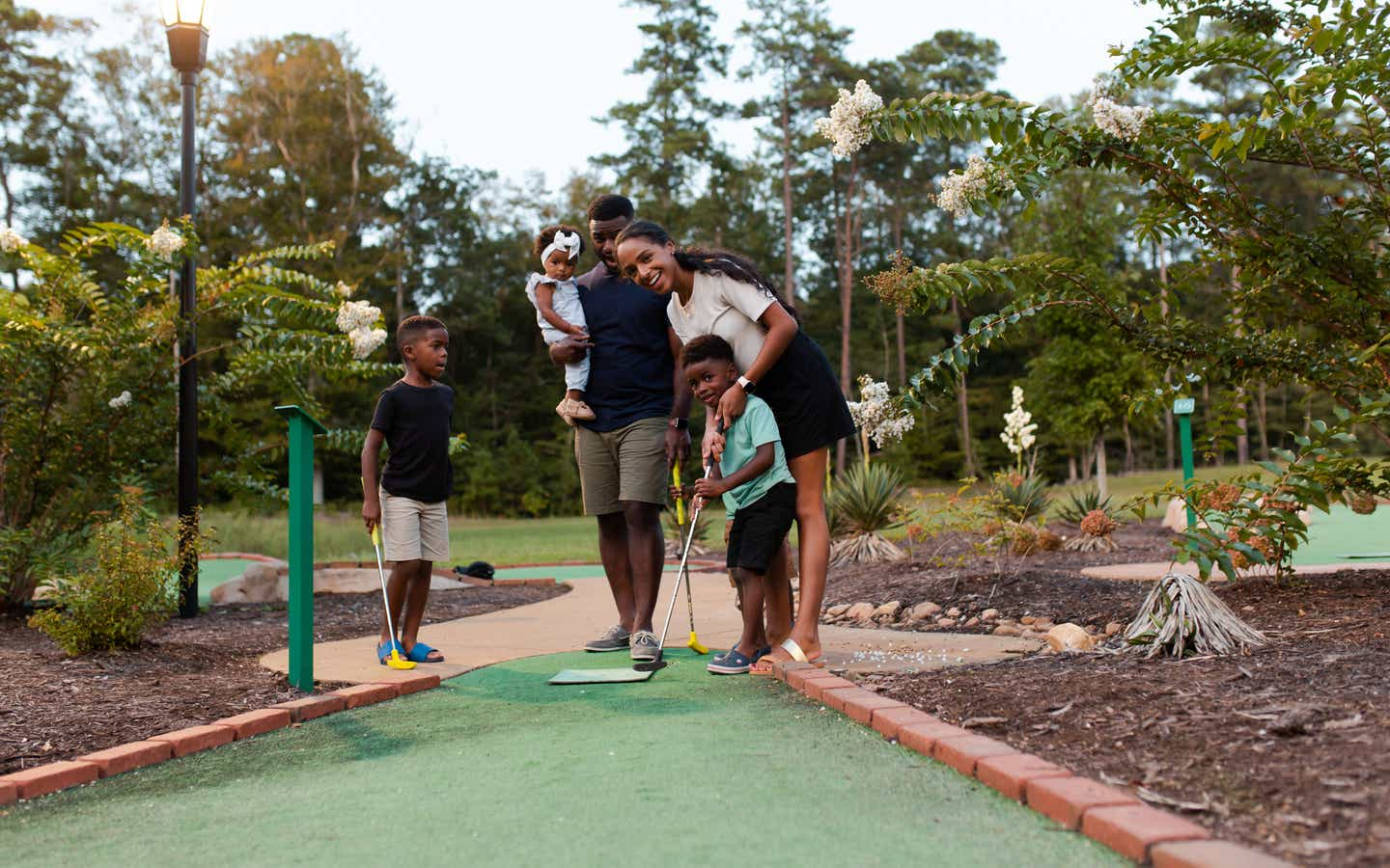 Family of five playing outdoor mini golf at Williamsburg Resort.