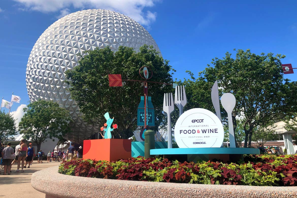 The Spaceship Earth attraction and Geosphere at Epcot stands behind a display garden at the front entrance for the Epcot International Food & Wine Festival with Remy and Emile designs.