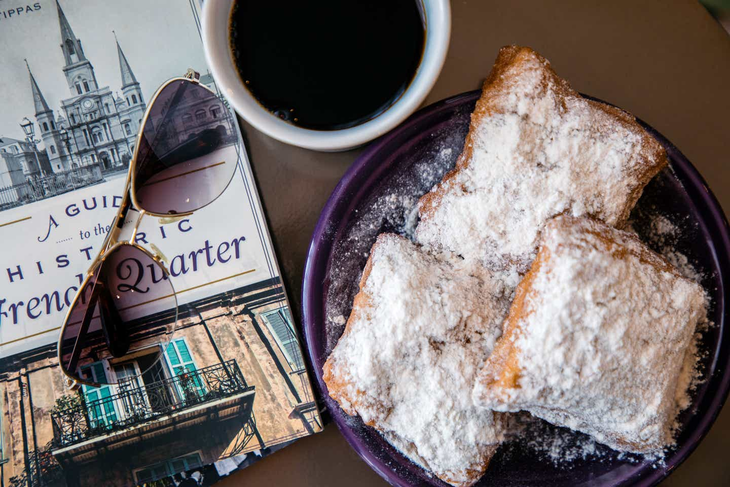 Beignets placed on a table next to a white mug full of coffee, sunglasses, and brochures that read 'A guide to the Historic French Quarter.'