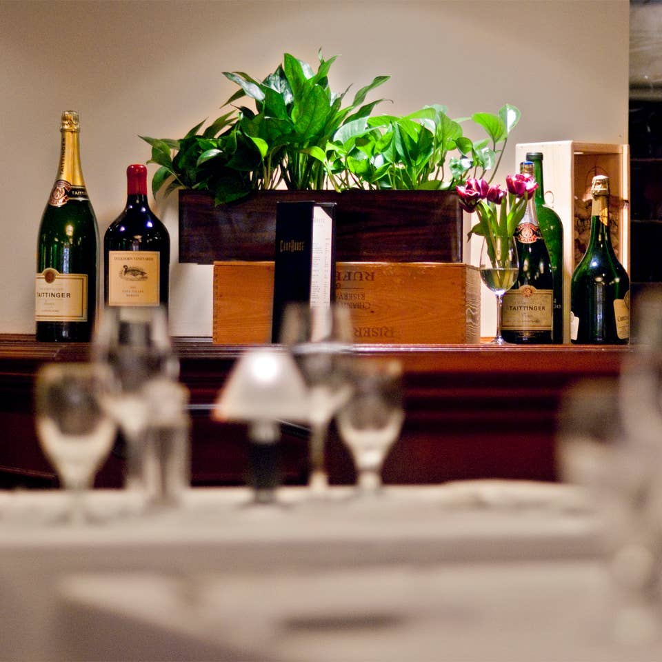 Restaurant table with wine glasses and bottles of wine in the background.