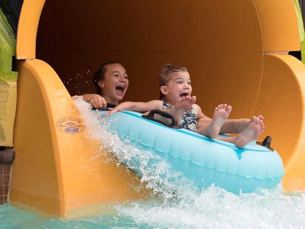 Two children going down waterslide in waterpark.