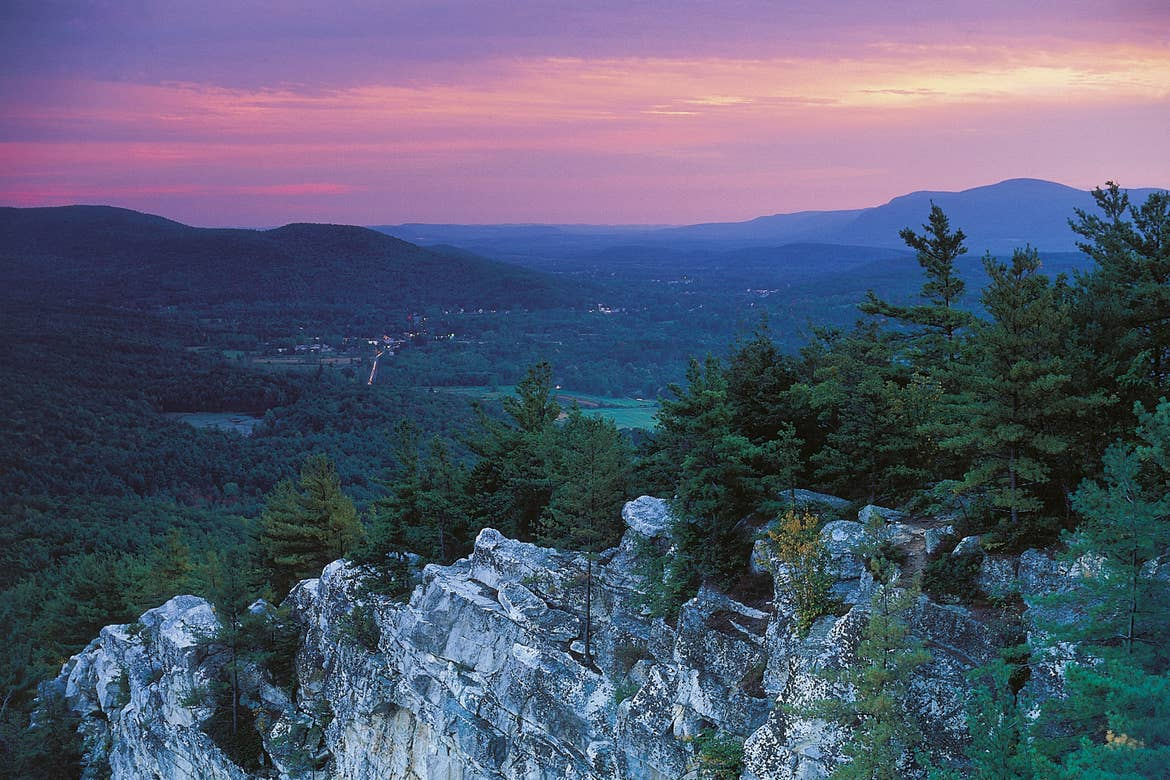 The summit of Monument Mountain in Great Barrington, MA with a purple sunset in the distance.