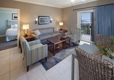Living room with couch, two accent chairs, and access to balcony in a two-bedroom villa at Galveston Beach Resort