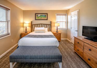 Bedroom with tv, dresser, and end tables in a one bedroom villa at Oak n' Spruce Resort in South Lee, Massachusetts