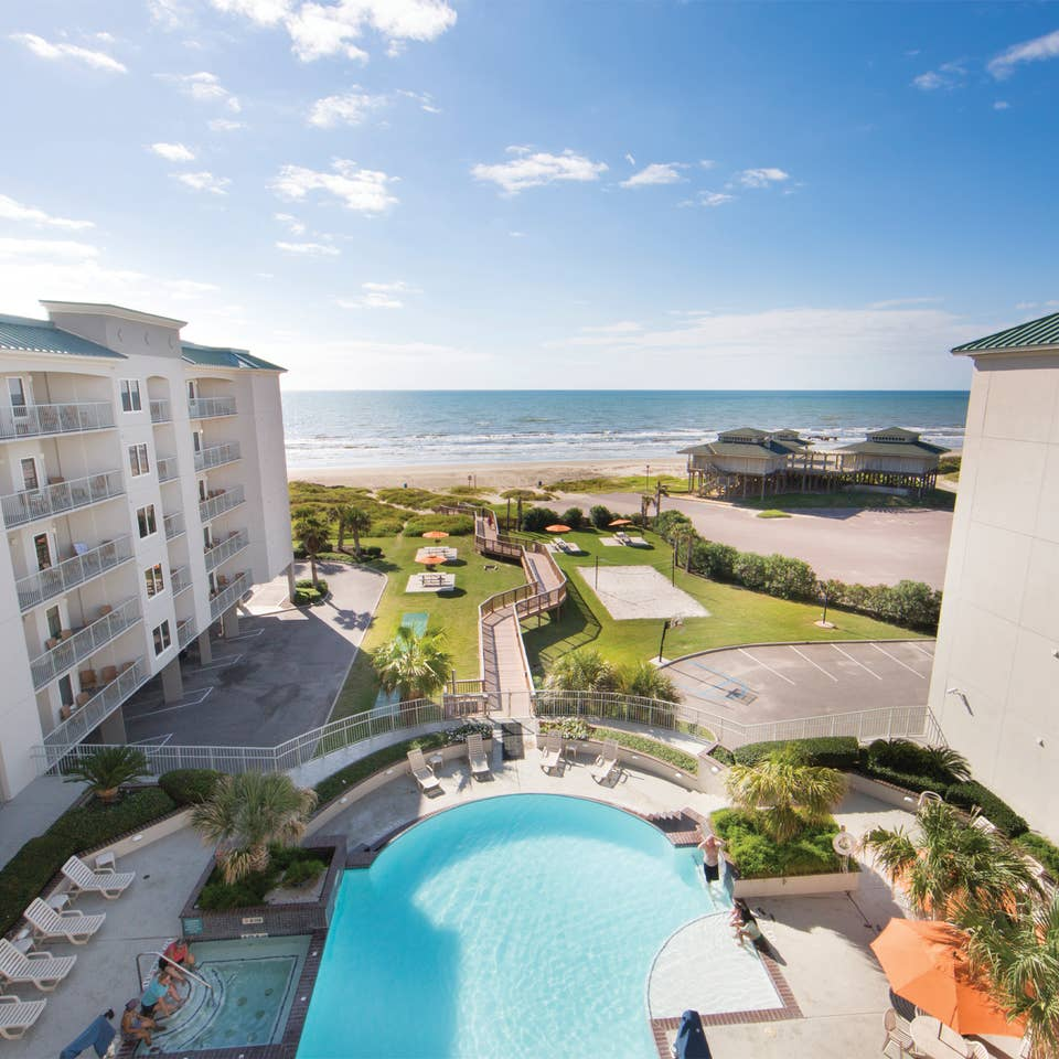 View of outdoor infinity pool and beach from Galveston Beach Resort room balcony in Texas.