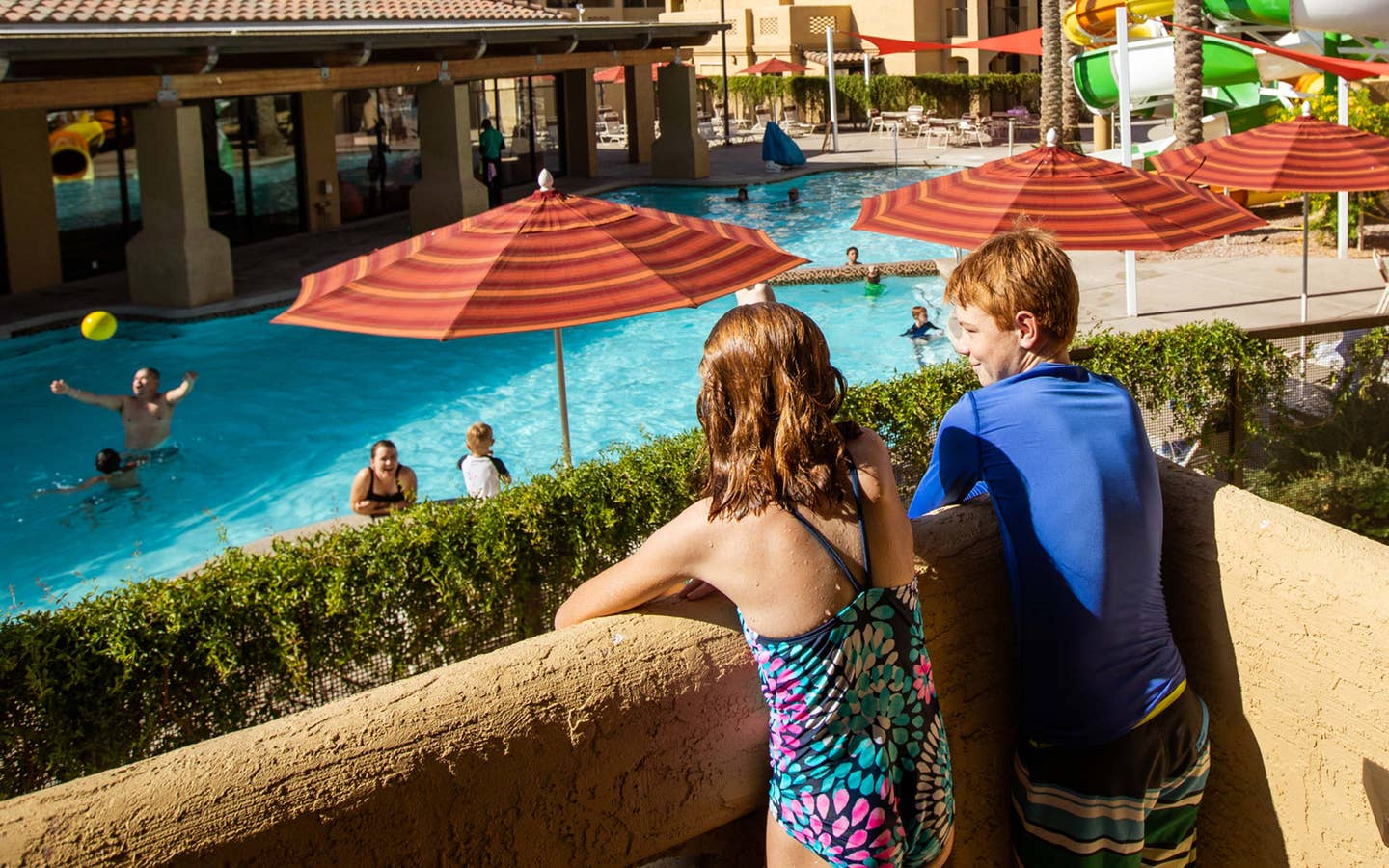 Two kids looking at pool and waterslide from balcony at Scottsdale Resort in Arizona.