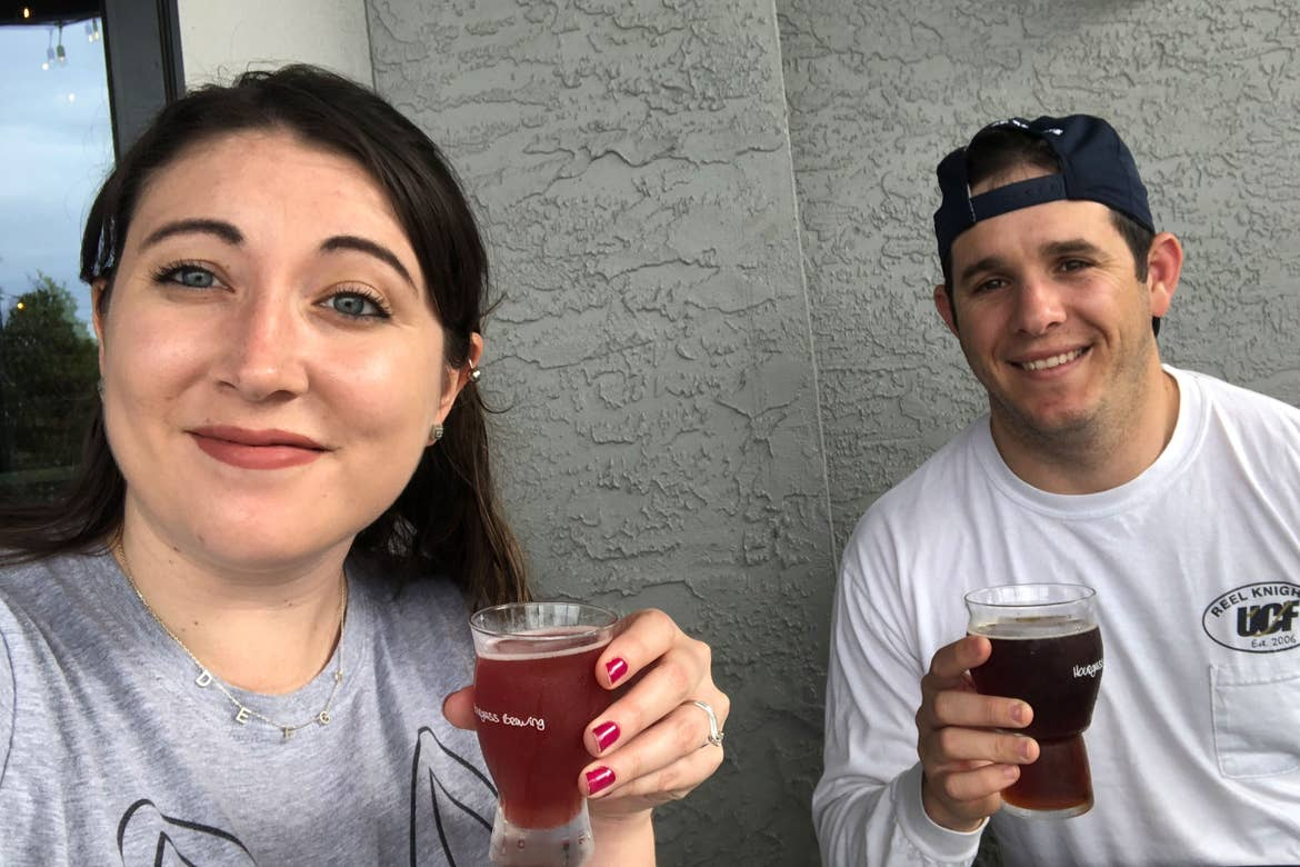 Featured Contributor and Checking In Editor, Tori Ferrante (left), and husband, Books (right), holding their beer outside of 'Hourglass Brewing Co.'