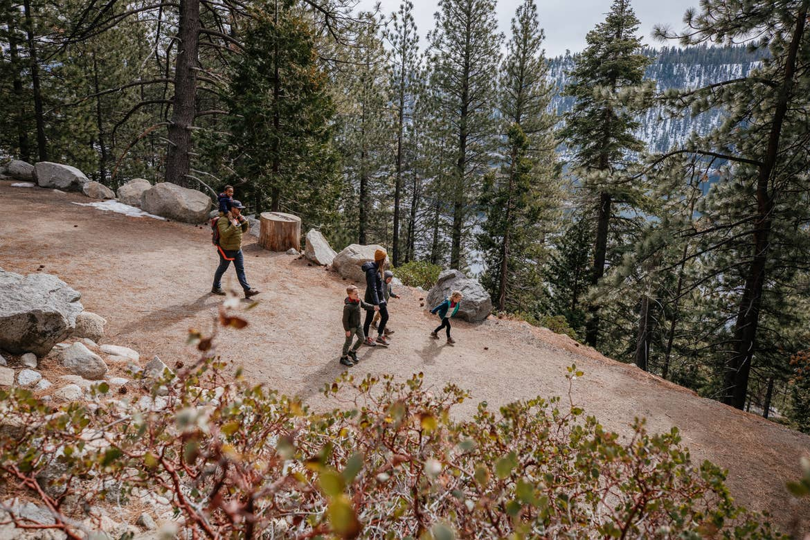 Featured Contributor, Andrea Rassmussen and her whole family take a stroll on a dirt trail surrounded by tall pine trees at Emerald Bay State Park in Nevada.