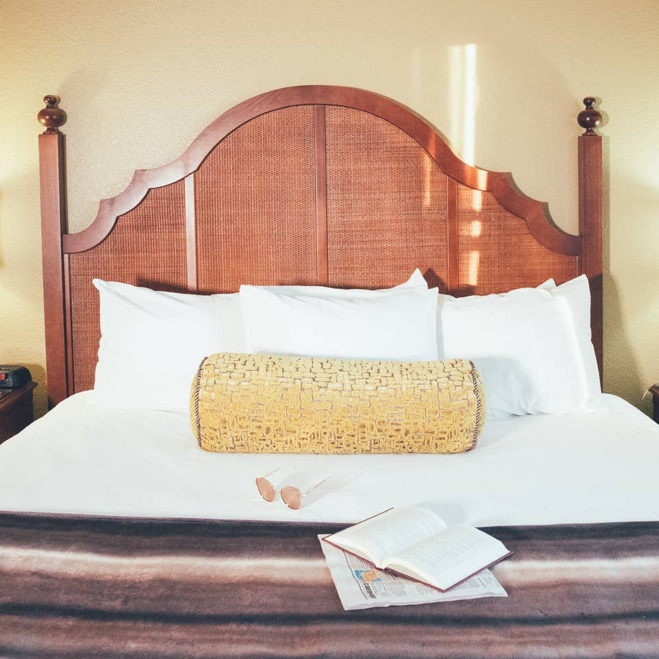 Bed with book and newspaper laying on top of covers in a Signature villa in River Island at Orange Lake Resort near Orlando, Florida